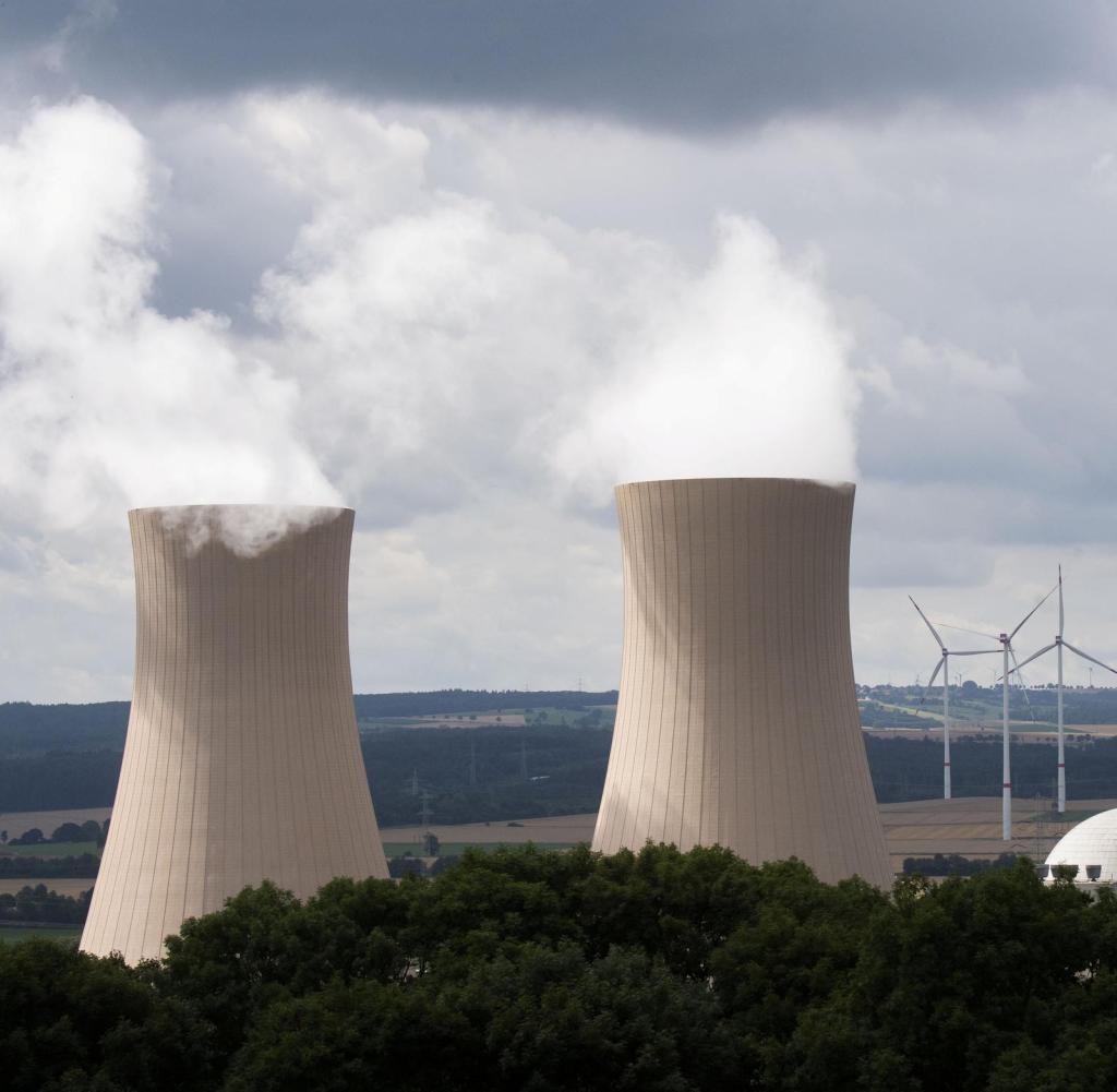 Il vapore sale dalle torri di raffreddamento della centrale nucleare di Grohnde a Hameln-Pyrmont, mentre sullo sfondo si possono vedere le turbine eoliche.