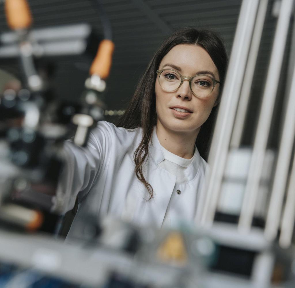 Primo piano di una scienziata che esamina le apparecchiature in laboratorio in fabbrica