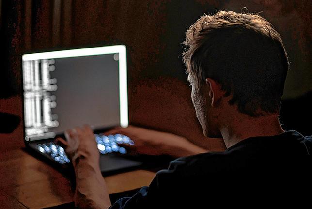 Uomo che scrive sulla tastiera del computer portatile.  Nell'ultimo attacco software di estorsione, gli hacker hanno preso di mira centinaia di aziende in un colpo solo.
