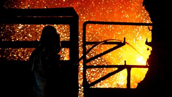 Un dipendente pulisce una siviera in ghisa presso l'acciaieria di Salzgitter AG.  © picture alliance / dpa Foto: Hauke-Christian Dittrich